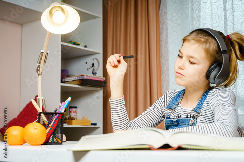Teenage using headphones and doing school homework, learning and studing concept Canvas Print