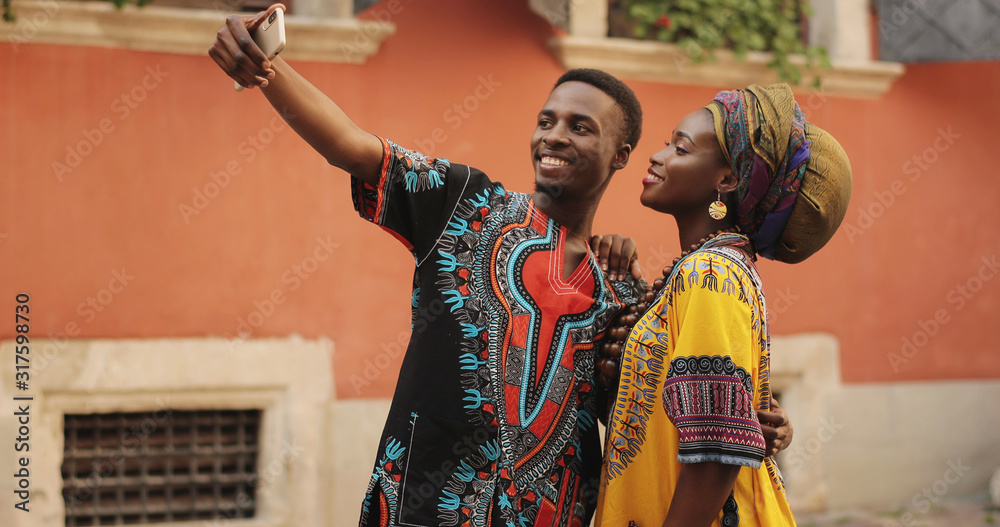 Fototapeta African young happy and good looking man and woman in traditional clothes standing together outdoor and taking selfie photos on the smartphone camera.