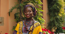 Portrait Shot Of The Beautiful And Happy Afrcan Woman In The Traditional Outfit Standing In The Cozy Courtyard With Flowers And Smiling To The Camera. Outdoor.
