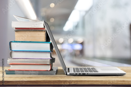 Stack of books with laptop on wooden table