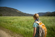 Woman walking on a meadow path through a valley in Rocky Mountain National Park, forested mountains in distance