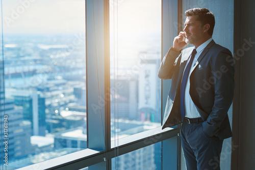 Cuadros en Lienzo Mature business CEO talking on phone alongside large high windows