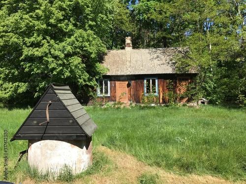 Piękny stary rozpadający się dom na Mazowszu w Polsce, na pierwszym planie stara studnia - wszystko zarośnięte zielenią
