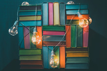 Colorful Fairy Books With Light Bulbs Illumination On Blue Background