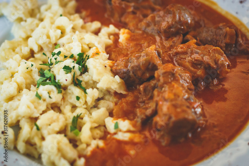 Fotografía Traditional hungarian and austrian dish - beef goulash with garnish egg noodles,