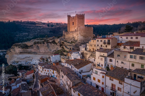 Sunset aerial panorama view of Alcala del Jucar medieval historic village with white washed houses and a castle on a rock in Albacete Spain