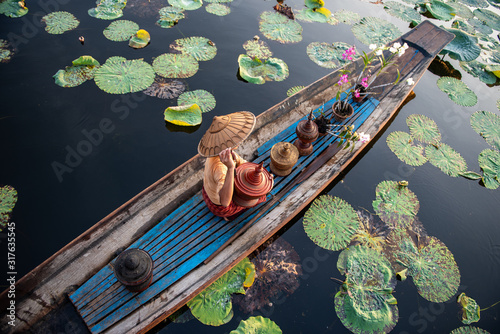 Canvas Print Burmese Intha woman in a rowing boat in the morning at In Dain Khone village, on Inle Lake, Myanmar