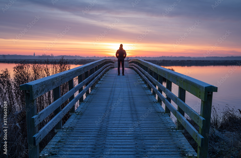 Fototapeta A man on a wooden bridge over a lake enjoying the view during a tranquil sunrise.