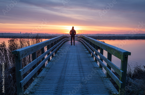 Платно A man on a wooden bridge over a lake enjoying the view during a tranquil sunrise