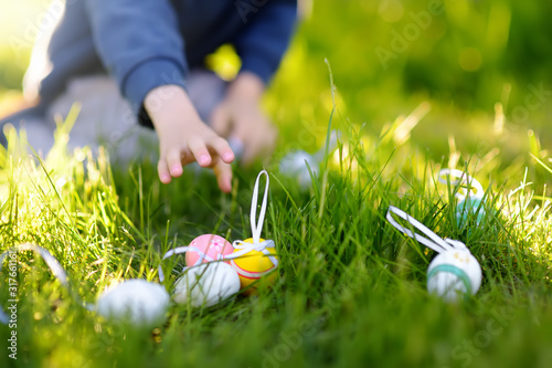 Little boy hunting for easter egg in spring garden on Easter day Canvas Print