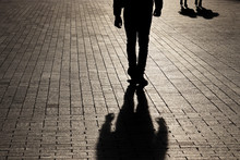 Silhouette And Shadow Of A Man Walking Walking Towards A Couple On A Street. Concept Of Crime Or Robbery, Relationships, Jealousy, Social Issues