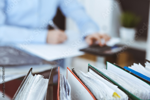Binders of papers waiting to process by bookkeeper woman or financial inspector, close-up Wallpaper Mural