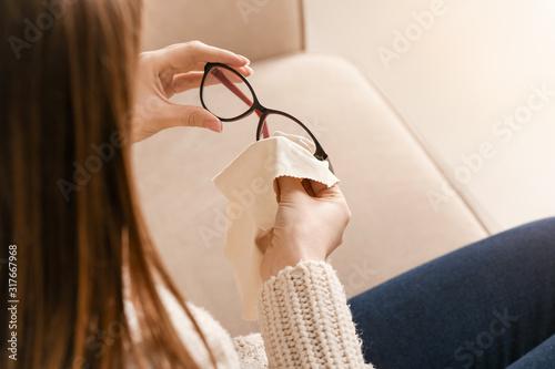 Obraz Young woman wiping eyeglasses at home, closeup - fototapety do salonu