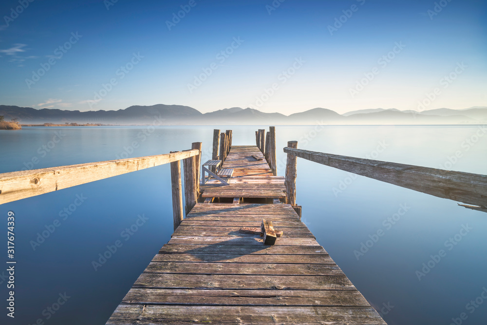 Fototapeta Wooden pier or jetty and lake at sunrise. Torre del lago Puccini Versilia Tuscany, Italy