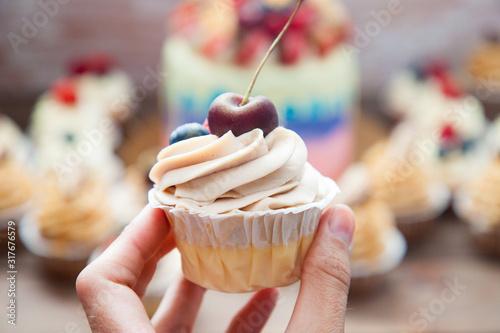Fototapeta Cheesecake cupcake with cream cheese frosting and fresh cherry on top obraz