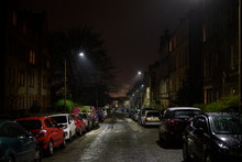 British Urban Streets At Night. Dark Alley Of Edinburgh City With Cars Parking On The Side Of The Road, Damp From The Rain. Downtown Apartment Buildings And Homes Neighborhood, Street Lights On.
