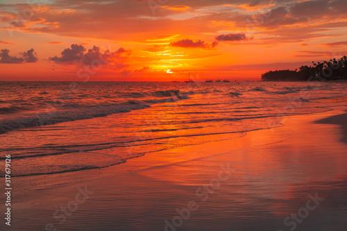 Bright orange sunrise over Atlantic Ocean. Bavaro beach, Punta Cana #317679126