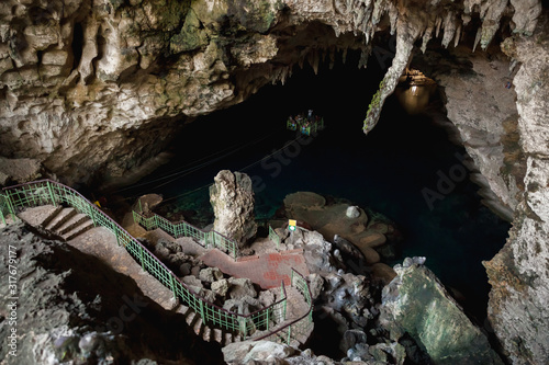 Underground lake and small ferry with tourists #317679177