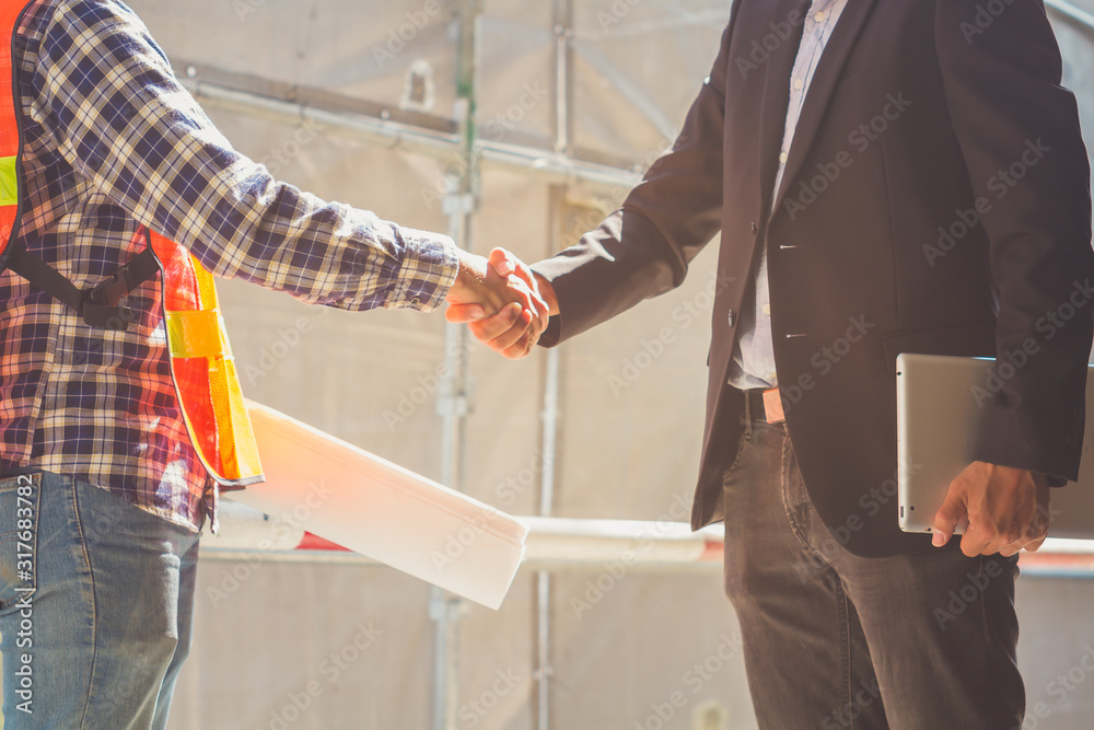 Fototapeta A businessman hold notebook and an engineer hold drawing plan shaking hands, successful in business negotiation deal , finishing up a project meeting at site construction. Handshake Business concept.