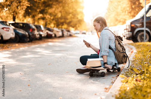 Obraz Female tourist sitting on long board with a map in the city and looking at phone. - fototapety do salonu