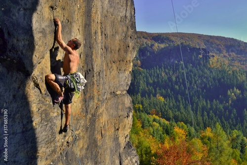 Obraz Young man is climbing on the sandstone rock in Sachsen Switzerland. Beautiful autumn day in Germany. - fototapety do salonu