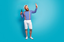 Full Body Photo Of Crazy Redhair Beard Man Have Holiday Relax Blogging Make Selfie Show His Bottle Beer Wear Orange Suspenders White Shorts Sun Headwear Isolated Blue Color Background