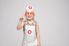 Cropped View Of Funny Little Girl Wearing Doctor Uniform Looking At Camera And Shoring Sign Of Silence. Preschool Child Playing Nurse And Enjoying Game On Isoalted Background. Concept Of Fun And Joy.