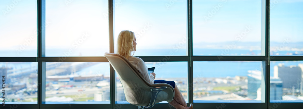 Fototapeta Businesswoman sitting in an office looking out at the city