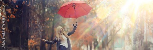 Fototapeta autumn look, sunny day a young girl with an umbrella walks in a yellow park in October obraz