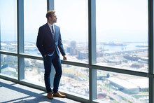 Young Business Achiever Looking Out Of High Office Window