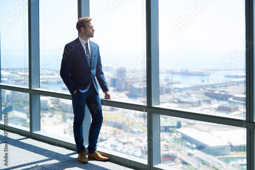 Photo Young business achiever looking out of high office window