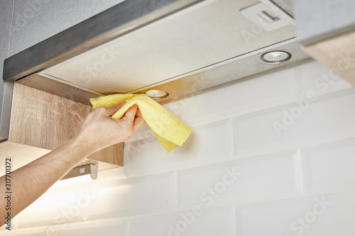Fotomural Hand cleaning kitchen hood with yellow washcloth