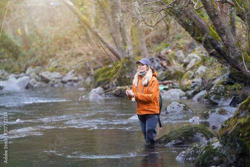 Fototapeta woman fly fishing in river