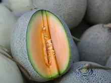 Whole And Cut Off Slice Of Japanese Melons, Fresh Orange Melon Or Cantaloupe Melon For Sale On Farm Market.