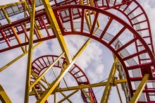 Low Angle Shot Of A Roller Coaster Ride With A Cloudy Sky In The Background