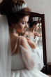 Morning preparation before wedding ceremony. Sexy girl. Beautiful sensual brunnete with elegant hairstyle. Wedding accessories. Fashion photo. Beautiful bride in white dress near a mirror.