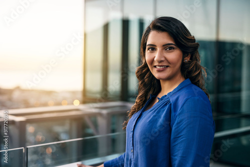 Smiing young businesswoman standing on an office balcony at dusk