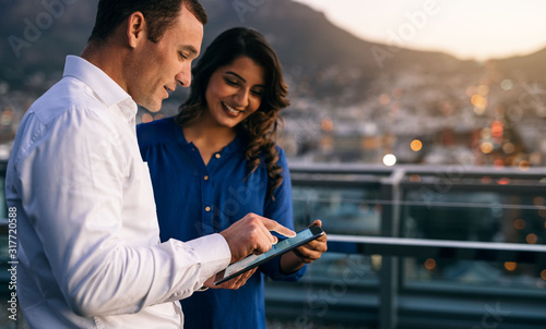 Diverse coworkers standing on an office balcony using a tablet