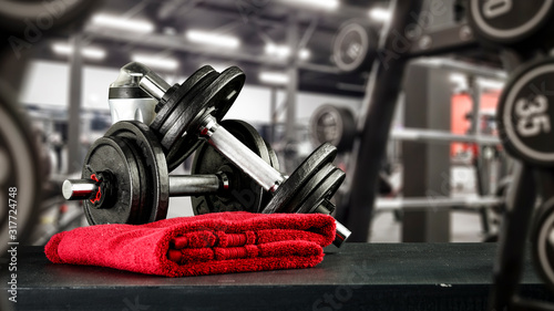 Fototapeta Black desk of free space for your decoration and blurred gym interior.Metal dumbbells and fit life