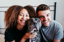 Happy Couple In Love At Home. Afro American Woman, Caucasian Man And Their Pit Bull Dog Together. Family Concept