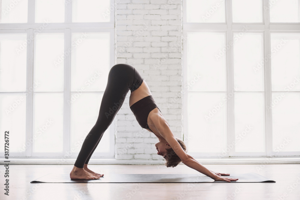 Fototapeta Young beautiful woman practicing yoga near floor window in yoga studio. Young beautiful girl doing exercises at home. Harmony, balance, meditation, relaxation, healthy lifestyle concept