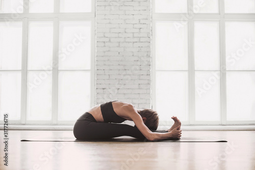 Carta da parati Young woman practicing yoga at class, working out, wearing sportswear, indoor, home interior background