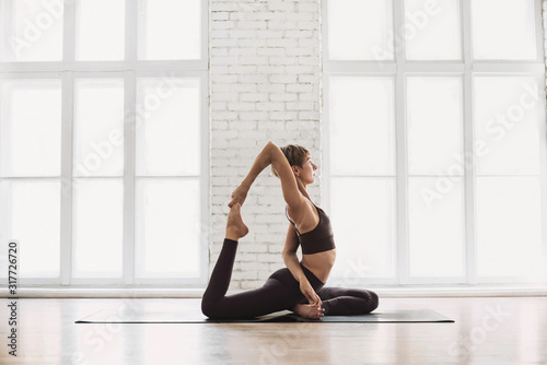 Obraz Young beautiful woman practicing yoga near floor window in yoga studio. Young beautiful girl doing exercises at home. Harmony, balance, meditation, relaxation, healthy lifestyle concept - fototapety do salonu