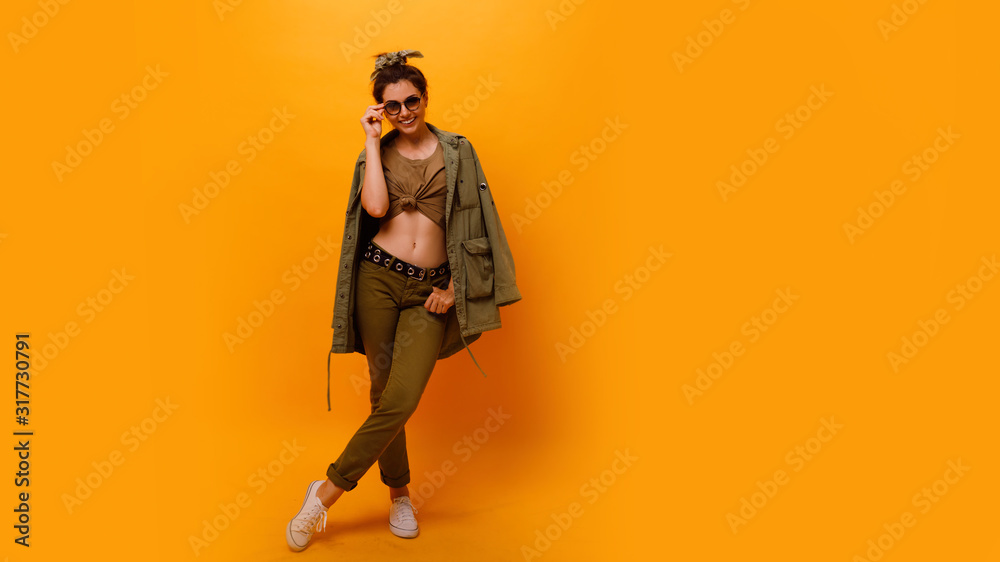 Fototapeta Full length Young fashion,stylish smiling brunette with bandana hair roll woman in the studio. Fashion trend apparel, safari style .Girl in high spirits in khaki clothes posing on orange background
