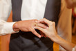 bride puts on a wedding ring to the groom
