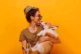 Fototapeta Zwierzęta -  Cute brunette woman in white t shirt and jeans holding and embracing Shiba Inu dog on plane red background. Love to the animals, pets concept. cheerful  woman holding Welsh Corgi puppy