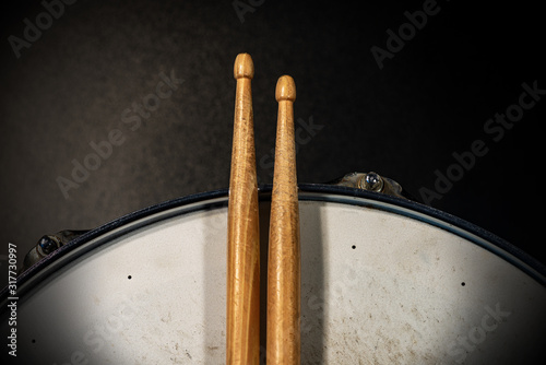 Close-up of two wooden drumsticks on an old metallic snare drum with dark background Fototapeta