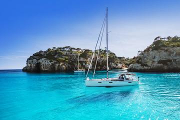 Prekrasna plaža s jahtom jedrilicom, Cala Macarelleta, otok Menorca, Španjolska. Koncept jahtanja, putovanja i aktivnog načina života