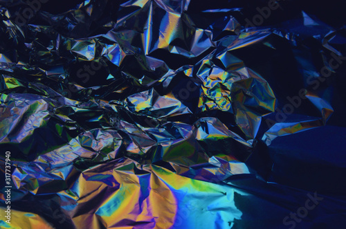 Holographic iridescent crumpled foil texture background © Anna