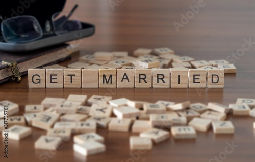 Photo get married concept represented by wooden letter tiles